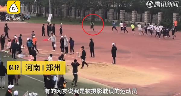 """▲大陆郑州工商学院的运动会上一位摄影师为了要记录场上运动员的精彩镜头,于是拿着摄影器材一起跟跑,但没想到跑着跑着竟超越选手,让现场民众傻眼,超惊讶他的""""快腿""""。(图/翻摄自腾讯影音)"""